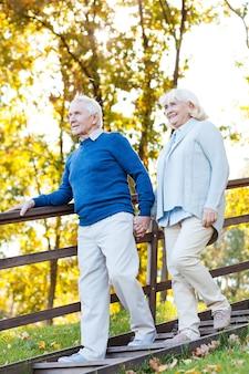 Casal sênior confiante. comprimento total do feliz casal sênior de mãos dadas e descendo por uma escada de madeira
