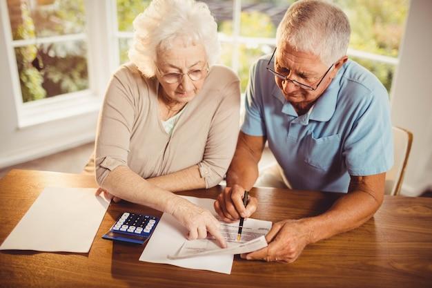 Casal sênior contando as contas em casa