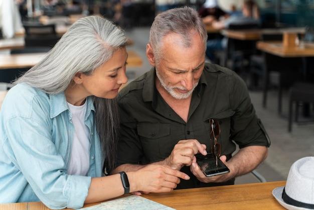 Casal sênior de tiro médio com smartphone