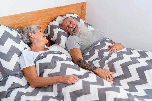 Casal sênior debaixo do cobertor em casa