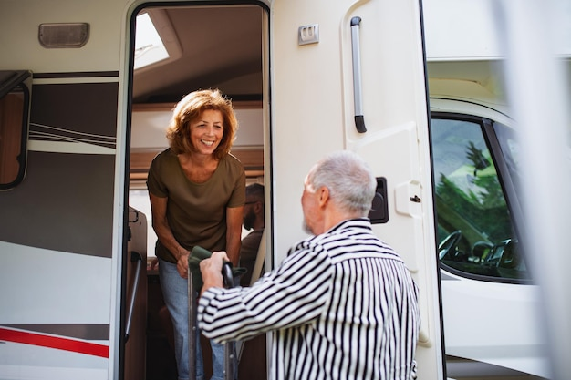Casal sênior desfazendo as malas e conversando de carro, viagem de férias de caravana familiar.