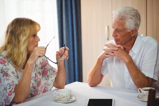 Casal sênior discutindo em torno de uma mesa