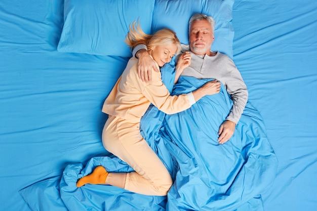 Casal sênior dorme pacificamente juntos no abraço na cama e tem um cochilo saudável em casa durante o sono de manhã cedo. família na hora de dormir e conceito de relaxamento