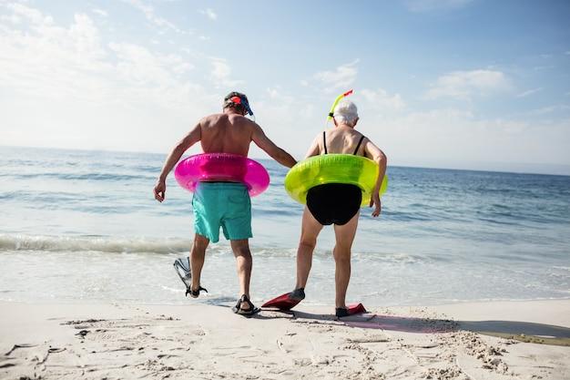 Casal sênior em anel inflável e nadadeira caminhando em direção ao mar