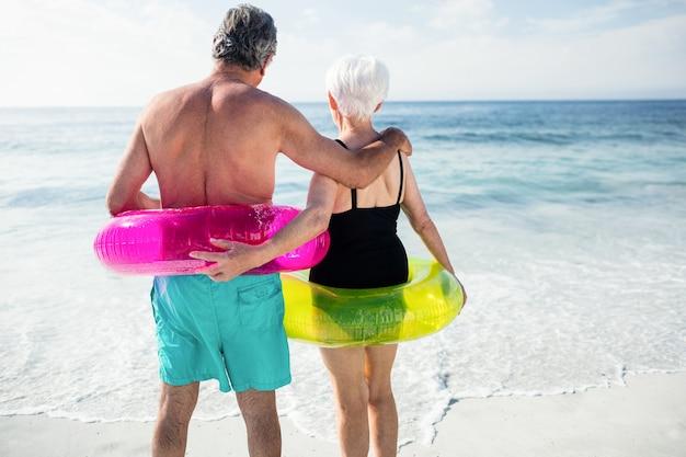 Casal sênior em anel inflável em pé na praia