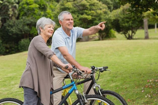 Casal sênior em bicicleta no campo