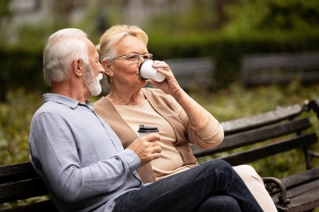 Casal sênior em dose média bebendo café
