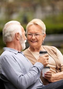 Casal sênior em dose média com café
