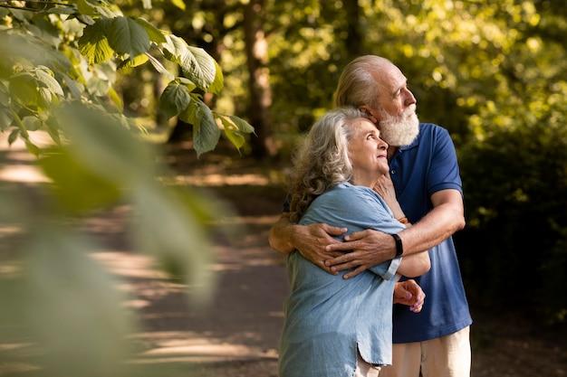 Casal sênior em foto média se abraçando ao ar livre
