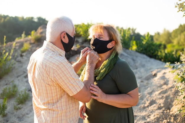 Casal sênior em máscaras médicas para proteger do coronavírus fora na natureza do verão, quarentena de coronavírus