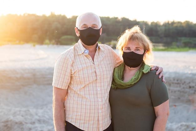 Casal sênior em máscaras protetoras do coronavírus do lado de fora, quarentena de coronavírus