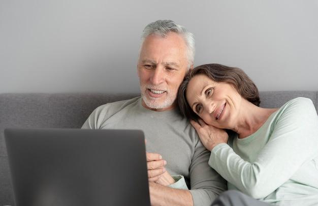 Casal sênior em plano médio com laptop