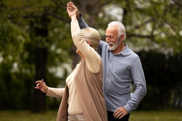 Casal sênior em plano médio dançando no parque