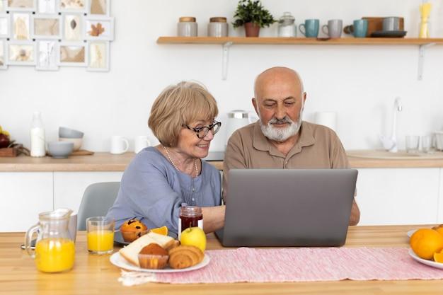 Casal sênior em plano médio sentado com um laptop