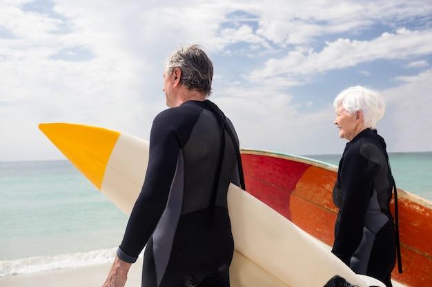 Casal sênior em roupa de mergulho segurando a prancha de surf na praia