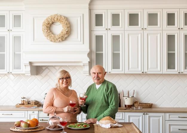 Casal sênior em tiro médio na cozinha posando