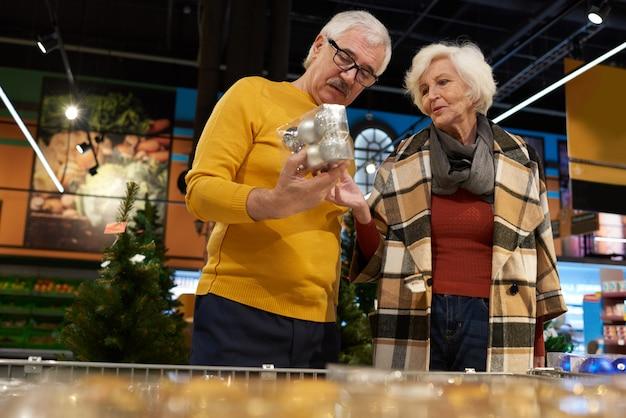 Casal sênior escolhendo decoração de natal
