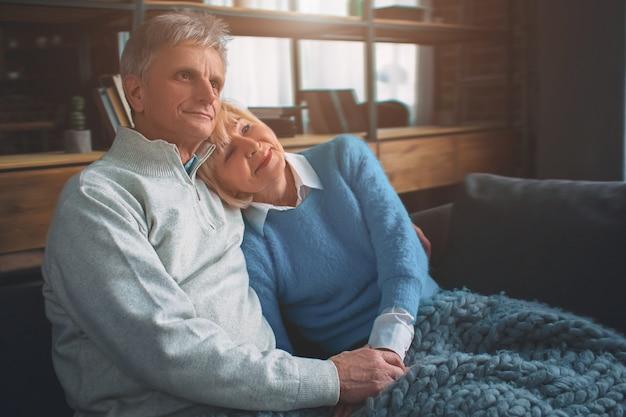 Casal sênior estão sentados juntos no sofá.