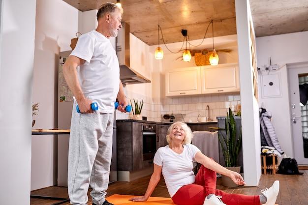 Casal sênior faz exercícios em casa juntos, ioga e malhação com halteres