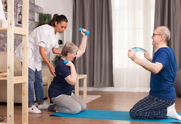 Casal sênior fazendo fisioterapia com médico.