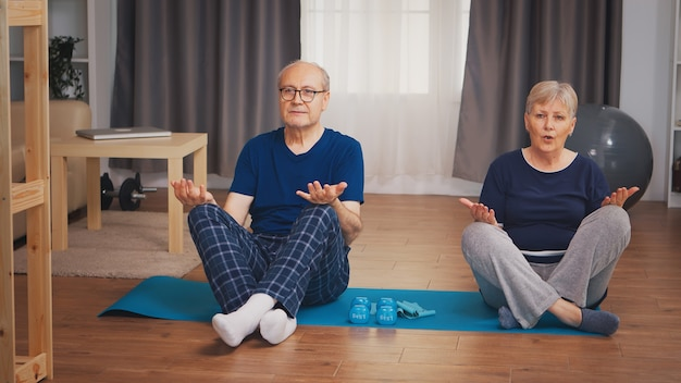 Casal sênior fazendo ioga sentado na esteira na sala de estar. idoso estilo de vida saudável, exercícios em casa, exercícios e treinamento, atividades esportivas em casa