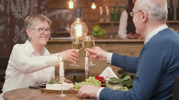Casal sênior fazendo um brinde com vinho pelo casamento. casal relaxado. jantar no restaurante.