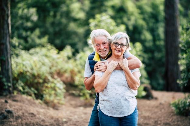 Casal sênior feliz e amoroso romântico apreciando o abraço em pé na floresta, sorrindo, marido abraçando a esposa por trás