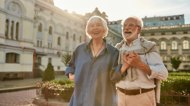 Casal sênior feliz e bonito de mãos dadas e sorrindo enquanto fica ao ar livre juntos