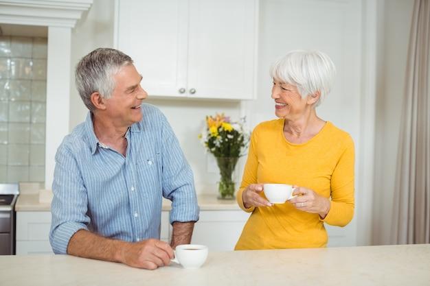 Casal sênior feliz tomando café na cozinha