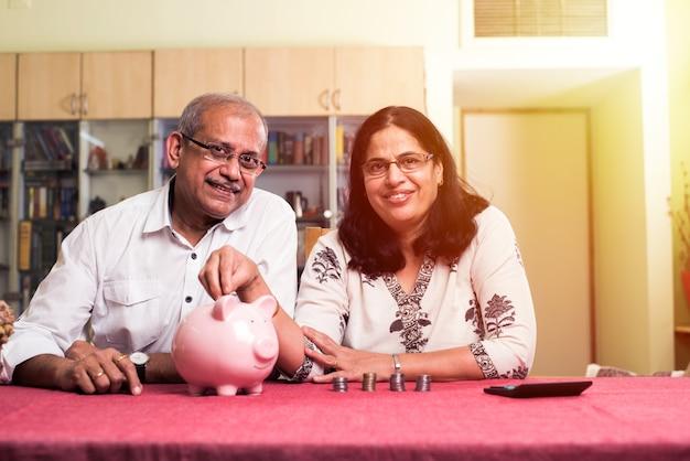 Casal sênior indiano asiático contando, fazendo finanças domésticas e verificando contas com laptop, calculadora e dinheiro também com o cofrinho, enquanto está sentado no sofá, sofá ou mesa em casa