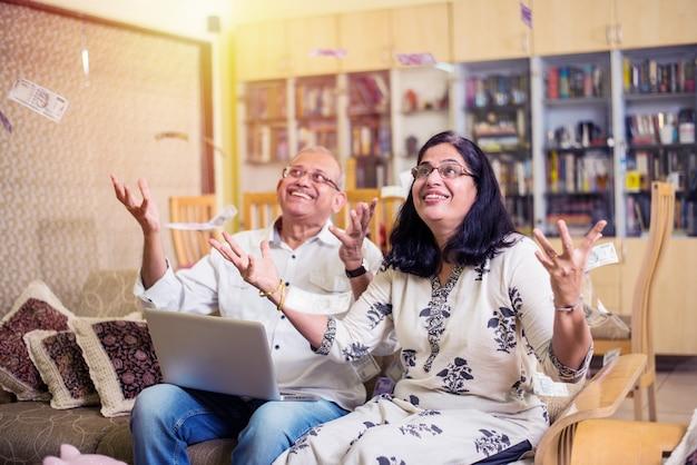 Casal sênior indiano asiático feliz tendo ganho na loteria ou um investimento em forma de dinheiro ou papel-moeda caindo do céu - conceito de chuva