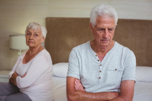 Casal sênior infeliz depois de discutir enquanto está sentado na cama
