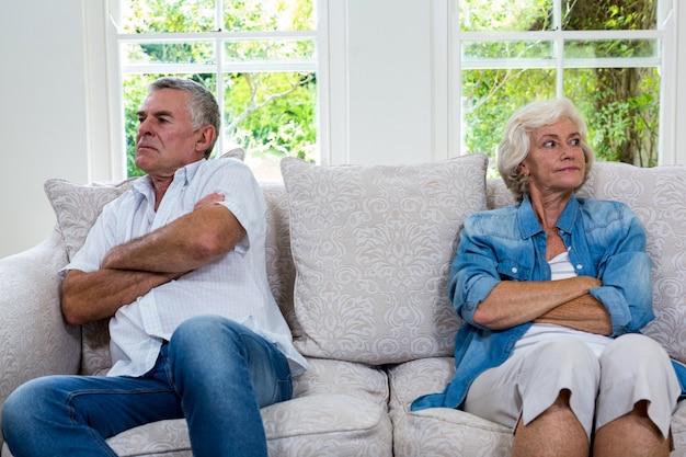 Casal sênior irritado, olhando para longe enquanto está sentado no sofá