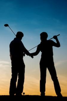 Casal sênior jogando golfe ao pôr do sol