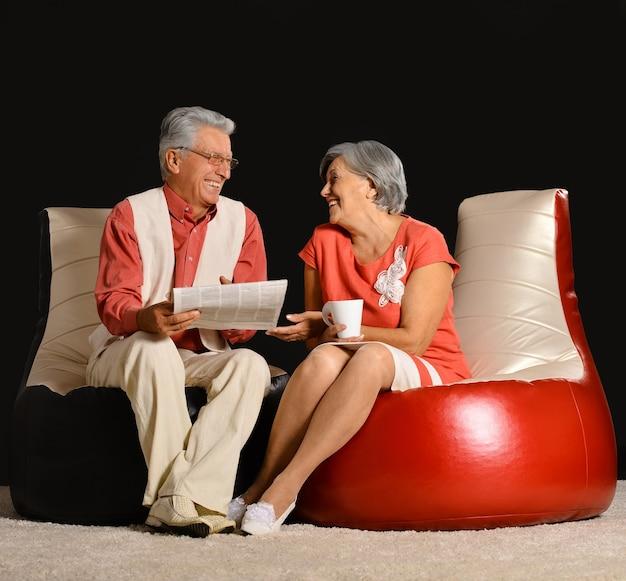 Casal sênior lendo jornal com café, sentado em uma poltrona vermelha sobre fundo preto