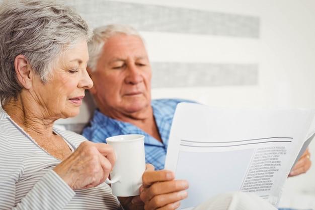 Casal sênior lendo jornal enquanto tomando café no quarto