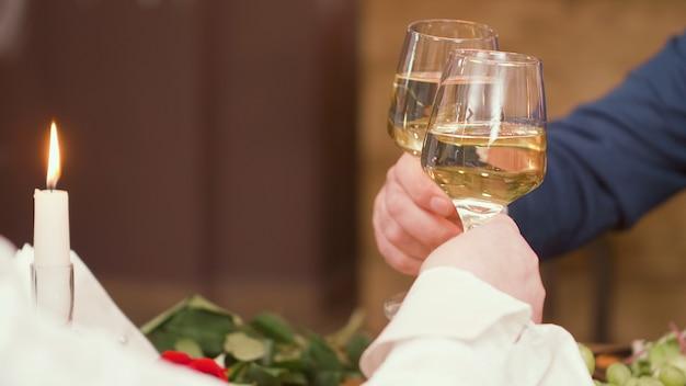 Casal sênior levantando torradas durante as refeições em um restaurante. casal relaxado. beber vinho.