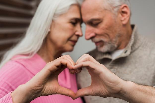 Casal sênior mostrando coração forma de mãos