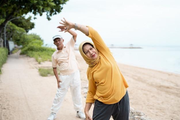 Casal sênior muçulmano fazendo alongamento e exercício ao ar livre