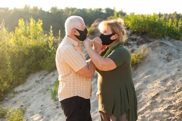 Casal sênior na praia usando máscara médica para proteger contra o coronavírus em dia de verão, quarentena de coronavírus