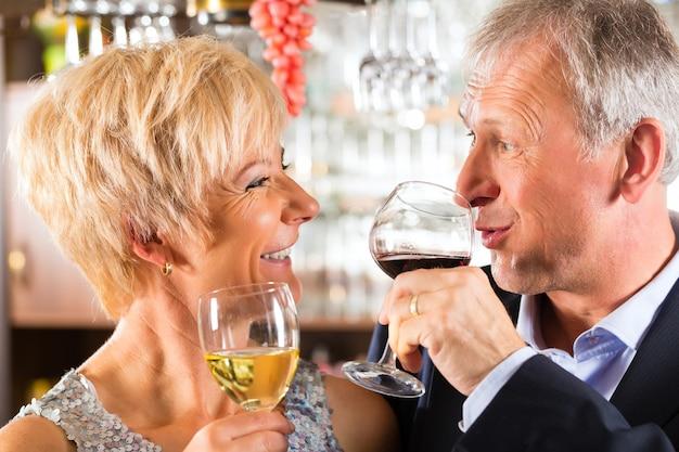 Casal sênior no bar com copo de vinho na mão