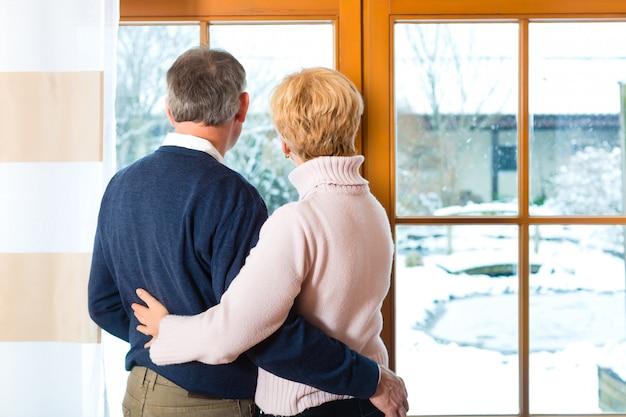 Casal sênior olhando ou da janela abraçando