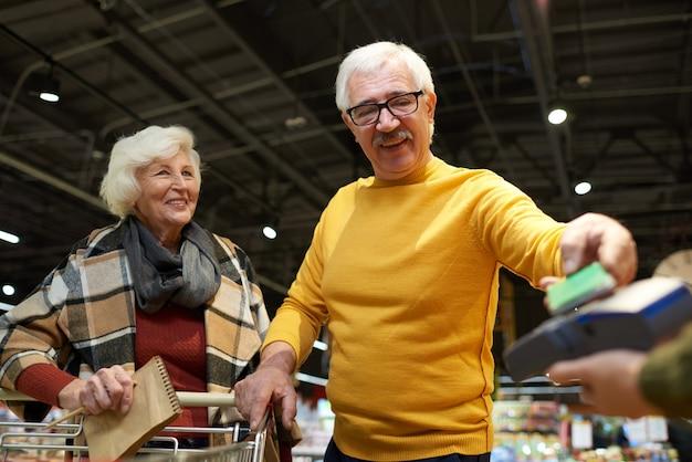 Casal sênior pagando no supermercado