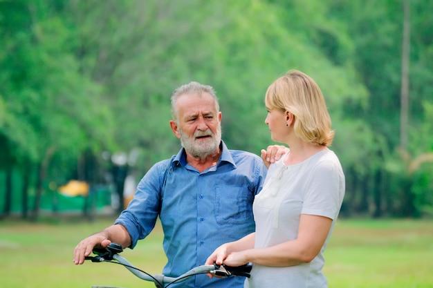 Casal sênior relaxe o estilo de vida no parque com bicicleta
