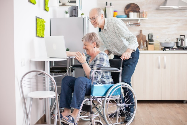Casal sênior rindo durante uma chamada de vídeo com os netos usando o computador tablet na cozinha. mulher idosa com deficiência e paralisada, usando a tecnologia de comunicação moderna.