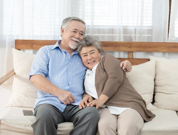 Casal sênior rindo enquanto está sentado no sofá em casa
