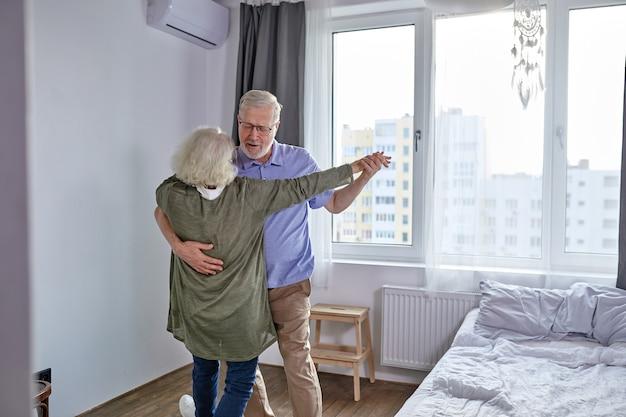 Casal sênior se diverte dançando em casa, romântico homem maduro de cabelos grisalhos e mulher se sentem energéticos e ativos, aproveite o fim de semana de aposentadoria em família, passem as férias juntos