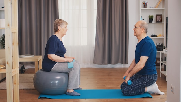 Casal sênior se exercitando usando tapete de ioga e bola de estabilidade. idoso estilo de vida saudável, exercícios em casa, exercícios e treinamento, atividades esportivas em casa