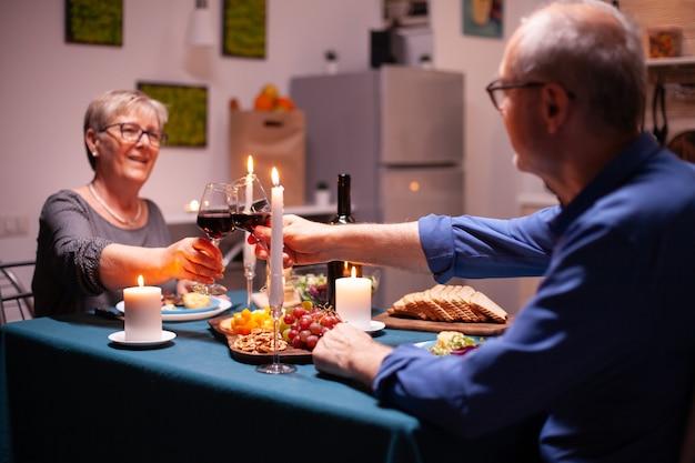 Casal sênior segurando taças de vinho durante a celebração do relacionamento na cozinha à noite. casal de idosos sentado à mesa da sala de jantar, conversando, apreciando a refeição,