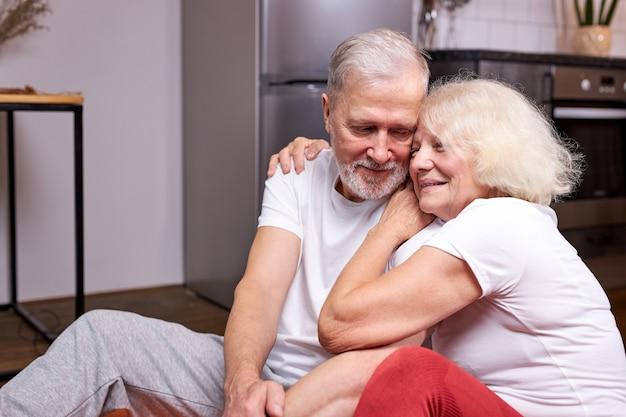 Casal sênior sentado, descansando no chão, após os exercícios esportivos juntos, gosta de ser saudável e esportivo, abraços com um sorriso